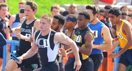 Male runners crowd the turn in a relay race at the 2016 State Championships.