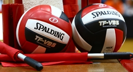 Two three-paneled red and black Spalding volleyballs and endline officials flags sitting on the head official's stand.