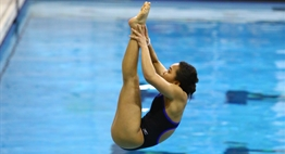A female diver performs a reverse pike during the 2017 State Championships.