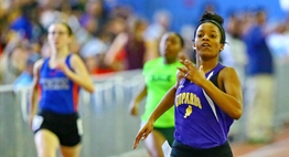 Female runners sprint towards the finish line at the 2017 State Indoor Track Finals.