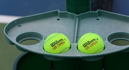 A courtside tray at the net holding Wilson tennis balls during the 2017 State Championships.