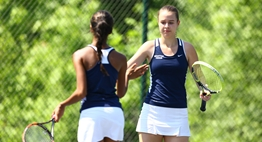 A female doubles team high fives one another after a point in the 2016 State Tennis Tournament.