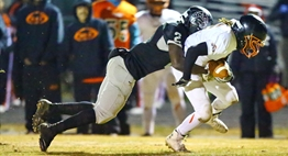 A DuVal ball carrier is tackled from behind by a Northwest defender in the 2015 State Semifinals.