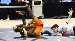 One wrestler prepares to pin another wrestler while the official is flat on the mat counting back points.
