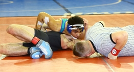A wrestling official lies prone while assessing the possibility of a pin in a 2016 State 4AA/3A bout.