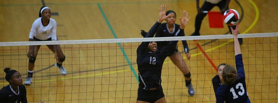 A female Bowie HS player attempts a kill at the net while a Northwest player attempts to block.