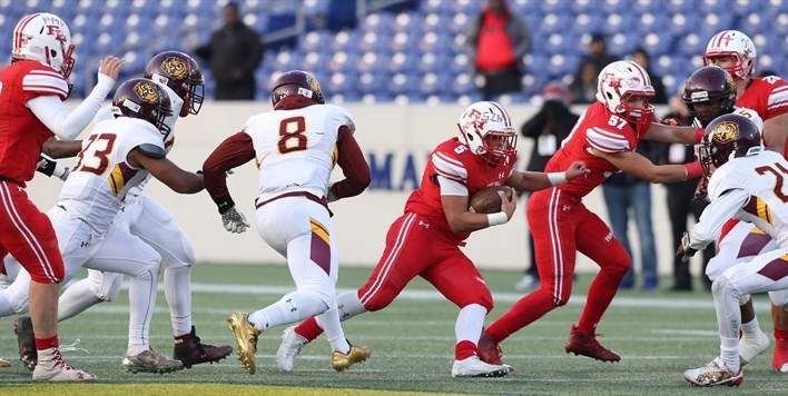 A Fort Hill football player follows his blockers through Dunbar's defense at the 2017 State Finals.