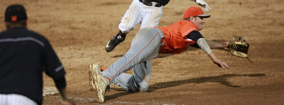 Fallston's third baseman dives to catch a throw as the Middletown baserunner begins his slide.