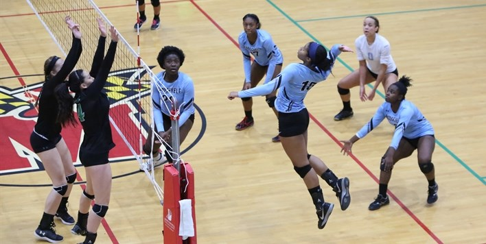A female volleyball player prepares to spike the ball as 2 defending blockers move towards the net.