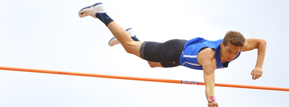 A male pole vaulter soars over the crossbar during the 2017 State Track and Field Championships.