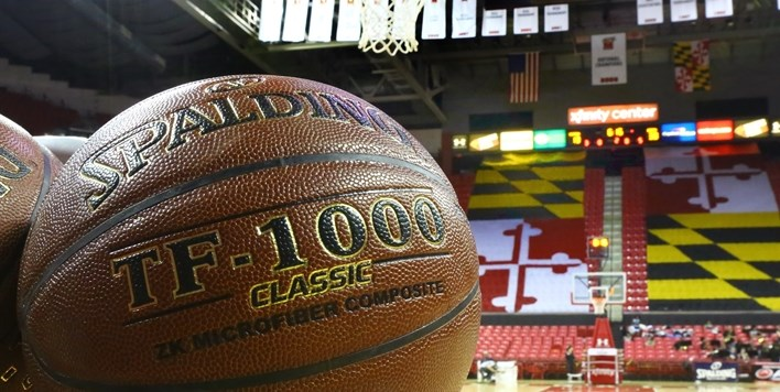Photo of the Spalding TF-1000 basketball on a ball rack with the Xfinity Center in the background.