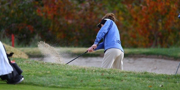 A female golfer blasts a shot out of the bunker in the 2015 State Golf Tournament.