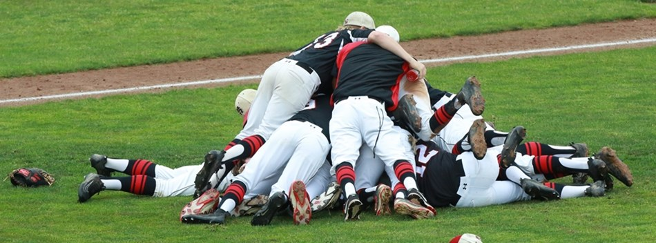 Saint Michael's baseball team pile on top of one another on the field after winning their game.