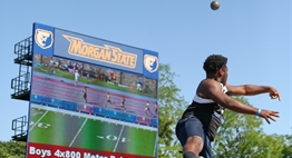 A male shotputter lets it fly with the video scoreboard as a backdrop at the 2018 State Meets.