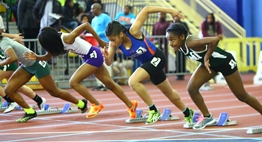 A group of female sprinters burst from the starting blocks in a 2016 State Indoor Meet race.