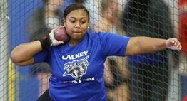 A female shotput athlete in mid-spin prior to releasing the shot during the 2018 State Championships.
