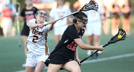 A female defender strains to check an offensive player cradling the ball in the 2018 State Lacrosse Finals.