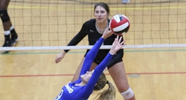 A setter arches her back while setting up the hitter behind her at the net during the 2017 State Tournament.