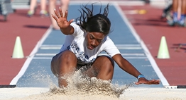 A female triple jumper lands in the sand pit at the end of her jump in the 2018 State Meet.