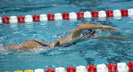 A female swimmer races freestyle during the 2019 State Swim Meets.