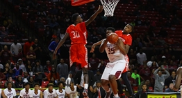 Two male Edmondson basketball players try to block the shot of a Fairmont Heights player in the 2017 Class 1A State Finals.