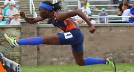 A female hurdler begins to clear a hurdle during a race in the 2017 State Championship meet.