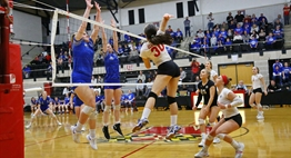 Defenders attempt to block an opponent's spike at the net during the 2018 State Finals.