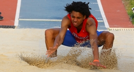 A male jumper hits the sand in the pit on his landing at the 2016 State Championship Meets.