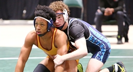 Two male wrestlers are poised to restart as they await the referee's signal at the 2019 State Tournament.