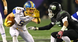 A Walkersville ballrunner stiff arms a Patuxent defender in 2015 State Finals.