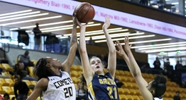 A female B-CC basketball player's shot is blocked from the side by a Catonsville defender in the 2018 State Tournament.
