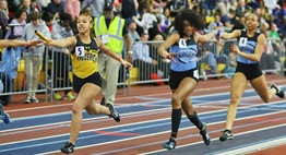Female relay runners try to hand off their batons during the 2019 State Championships.