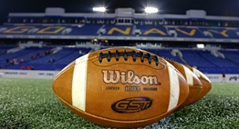 Wilson footballs lined up under the lights on the field at Navy-Marine Corps Memorial Stadium.