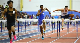 Three hurdlers racing to finish line.
