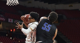 A Lake Clifton male basketball player snares a rebound in front of a North Caroline player in the 2018 State Finals
