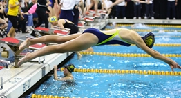 A female swimmer dives into the pool during a State Meet relay race in 2016.