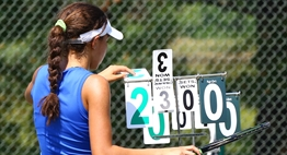 A female tennis player adjusts the flip score at her 2016 State Tournament match.