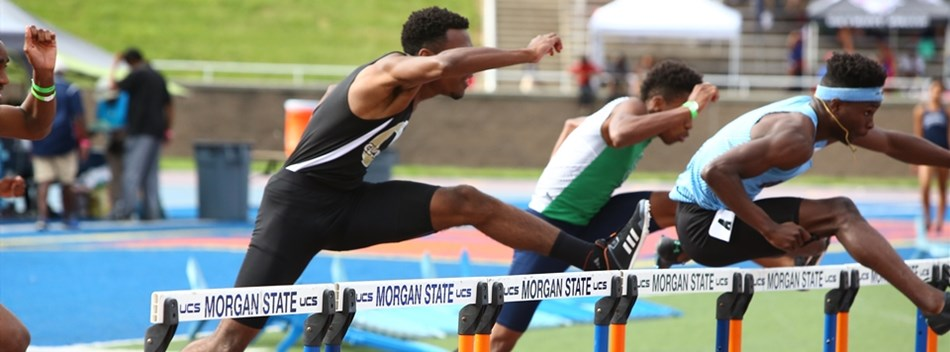 Male hurdlers stretch over the hurdles in a race at the 2019 State Track and Field Meets.