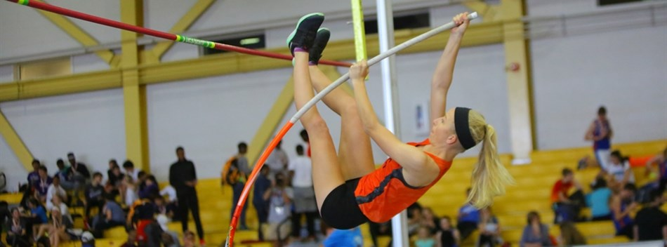 A female pole vaulter prepares to clear the bar at the 2017 Class 2A & 1A State Indoor Track Meets.