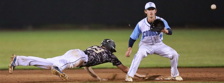 A Poolesville baserunner dives back into second base against a Chesapeake fielder.