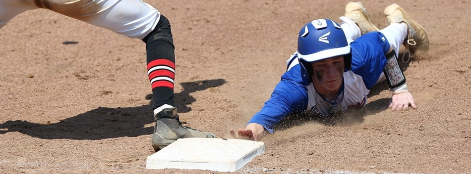 A base runner dives head first back into first base during the 2018 Class 1A State Baseball Finals.