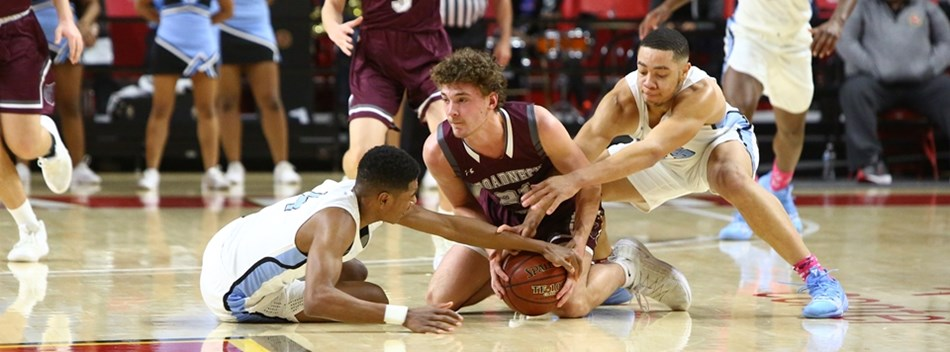 Male players scramble for a loose ball on the floor during the 2019 Class 4A State Semifinals.