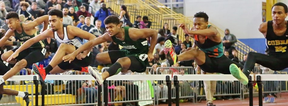 Male hurdlers race at the 2018 State Indoor Track & Field Championships.