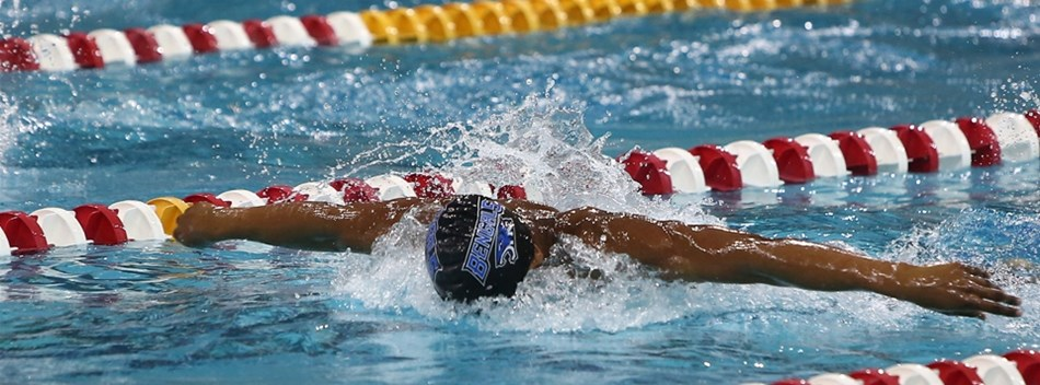 A picture of a male swimmer racing in the butterfly at the 2018 State Swimming Championships.