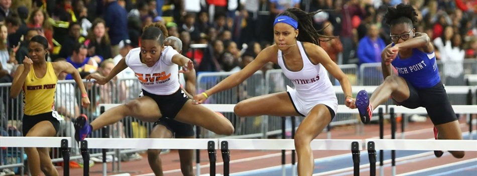Female hurdlers clear a hurdle during the 2019 Class 4A State Indoor Meet.