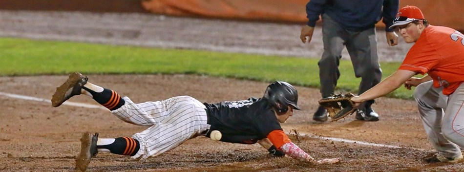 A Middletown baserunner dives back into first base to avoid a pick-off throw by Fallston.