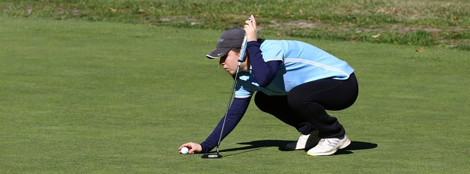 A female golfer lines up a putt during the 2018 State Finals.