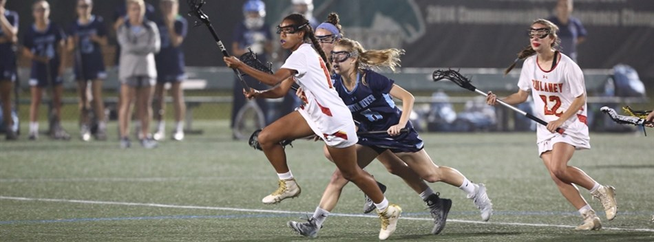 A player cradles the ball away from defenders during the 2018 Class 4A State Girls Lacrosse Final.