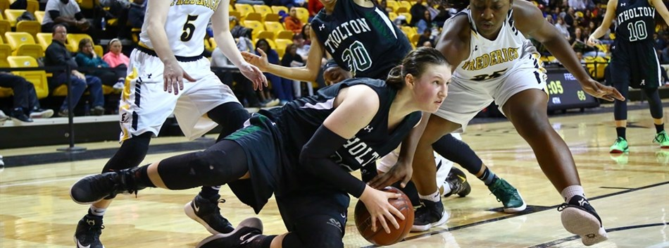 A female player from Atholton goes to the floor to recover a loose ball among several defenders.