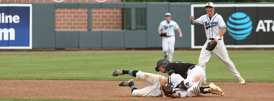 An infielder tumbles to the ground after successfully tagging the runner out at second base during t
